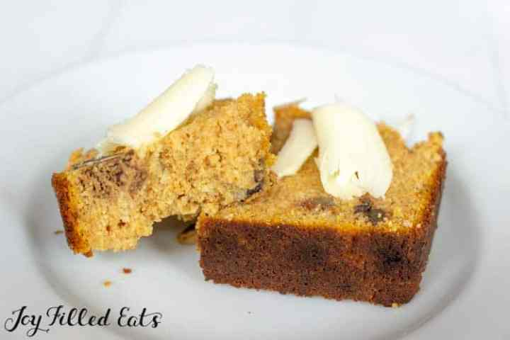 A slice of pumpkin bread on a white plate broken in half and topped with butter