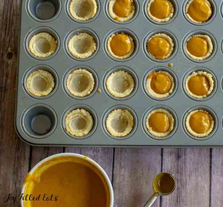 mini pie shells being filled with pumpkin pie filling
