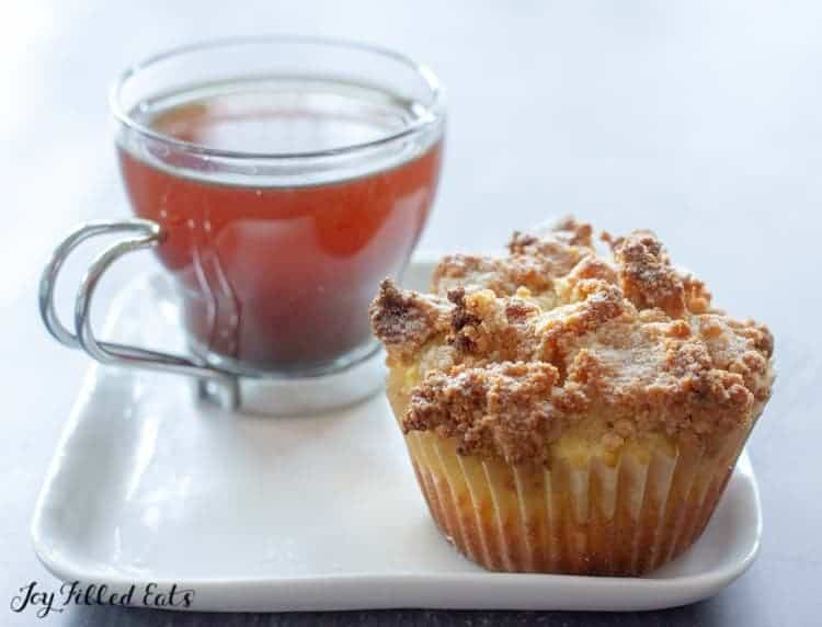 a coffee cake muffin and a cup of coffee on a white plate
