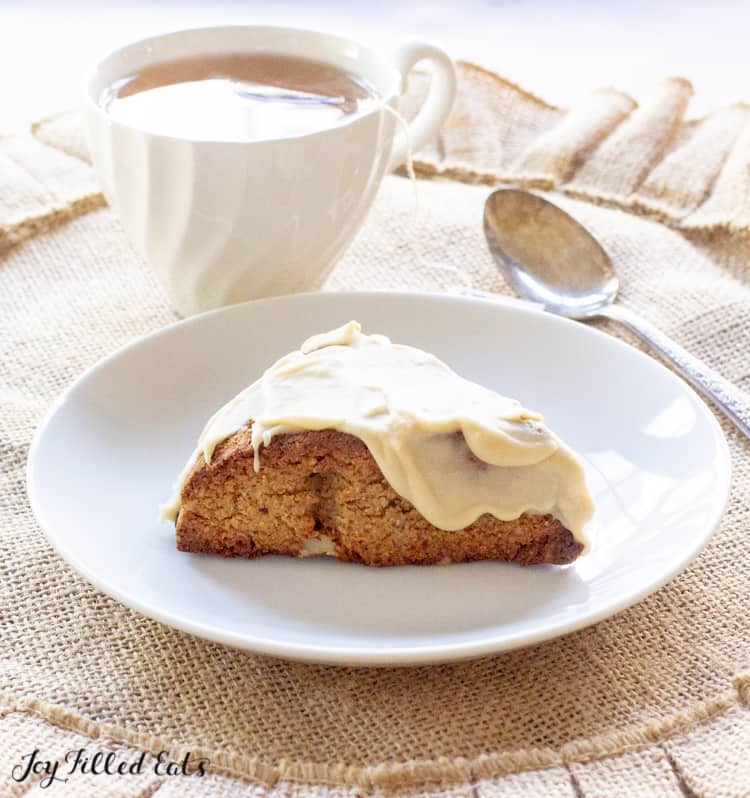 One of the maple pecan keto scones on a white plate with a cup of tea and spoon behind