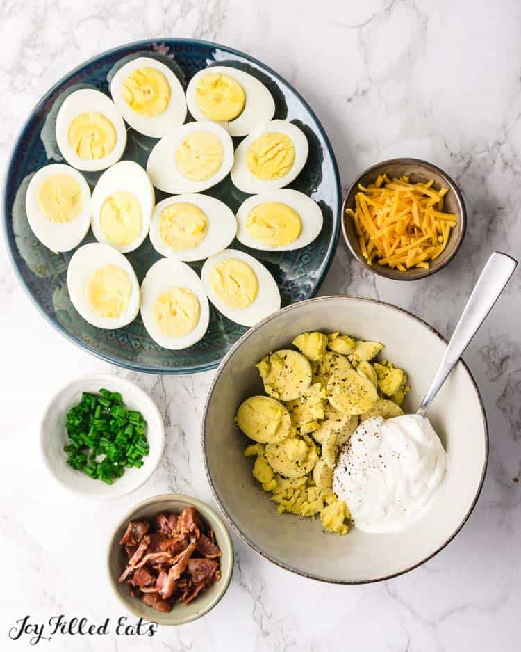 a plate of halved hard boiled eggs and the other ingredients needed for the keto deviled eggs with bacon