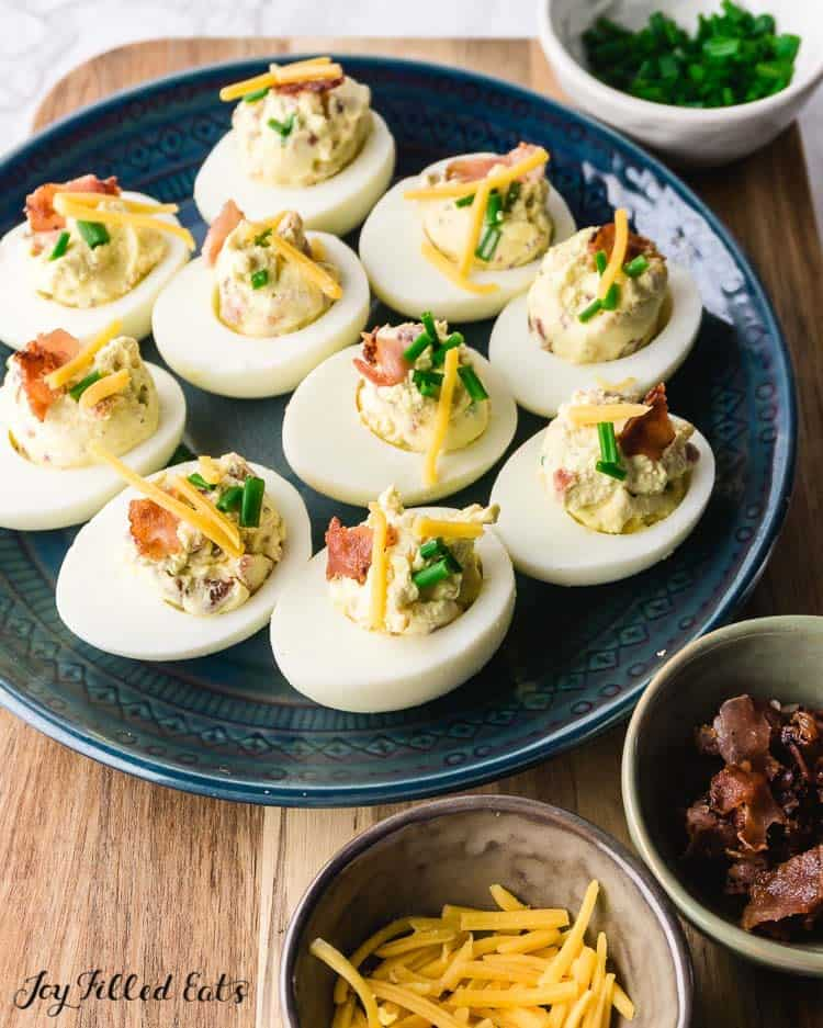 a blue plate of keto deviled eggs with bacon cheddar and chives