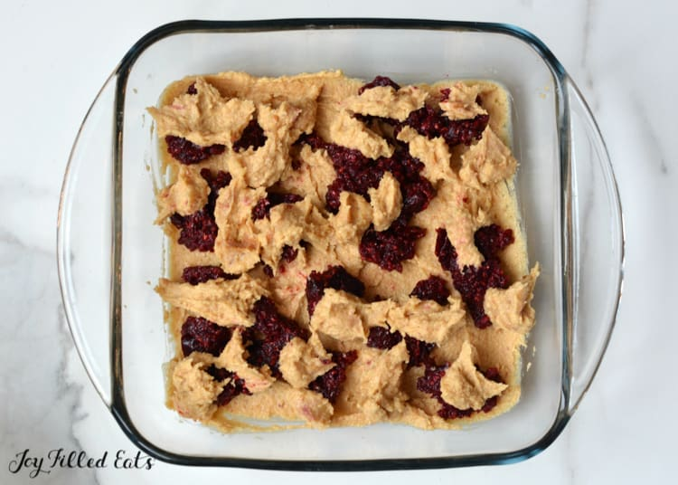 swirled raspberry jam in the peanut butter batter in a glass dish