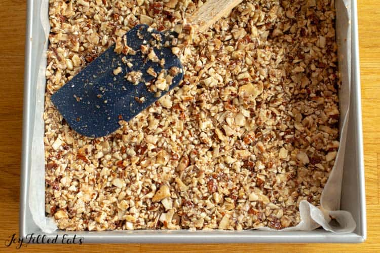 pressing the nut mixture for the homemade granola bars into a baking pan