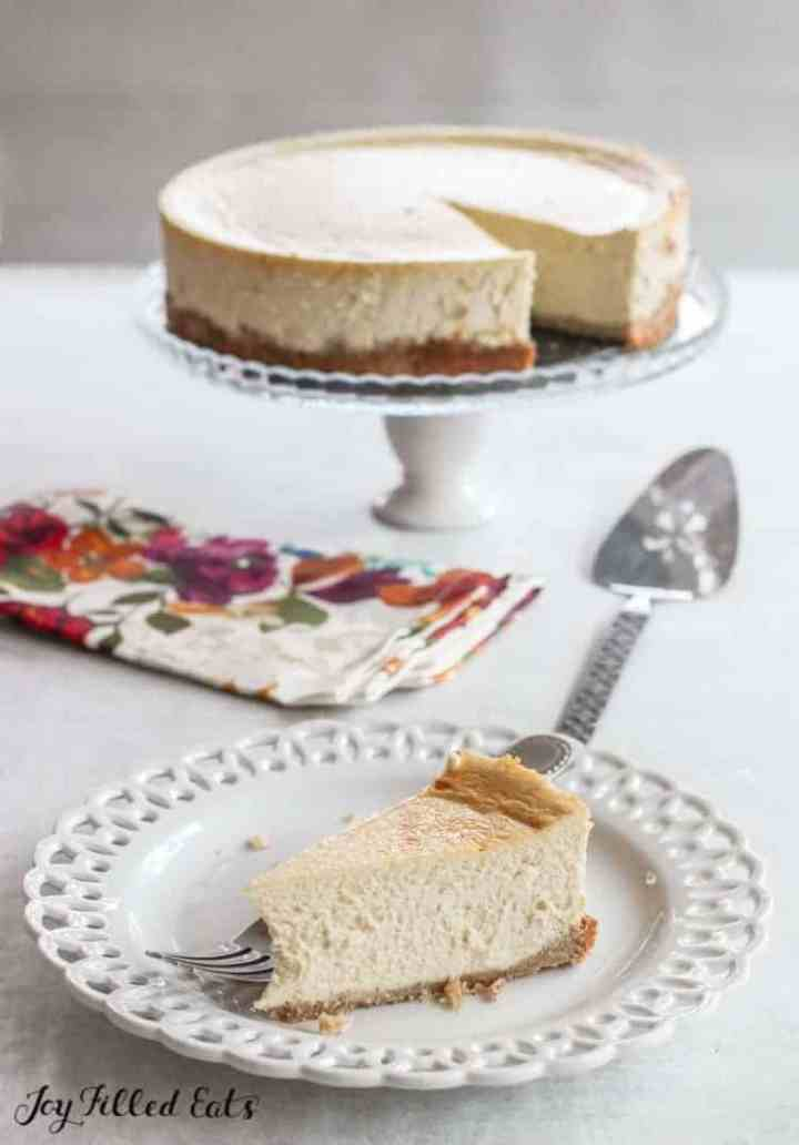 ricotta cheesecake on a white cake stand with a slice on a plate
