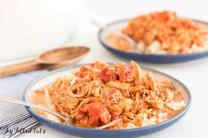 chicken tikka masala on top of cauliflower rice on a blue plate