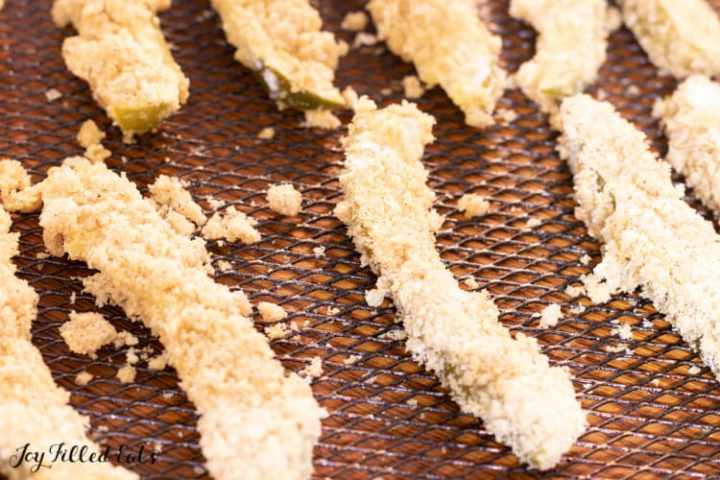 fried pickles turning golden brown on an air fryer tray