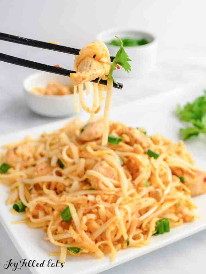 chopsticks lifting up a bite of chicken pad thai