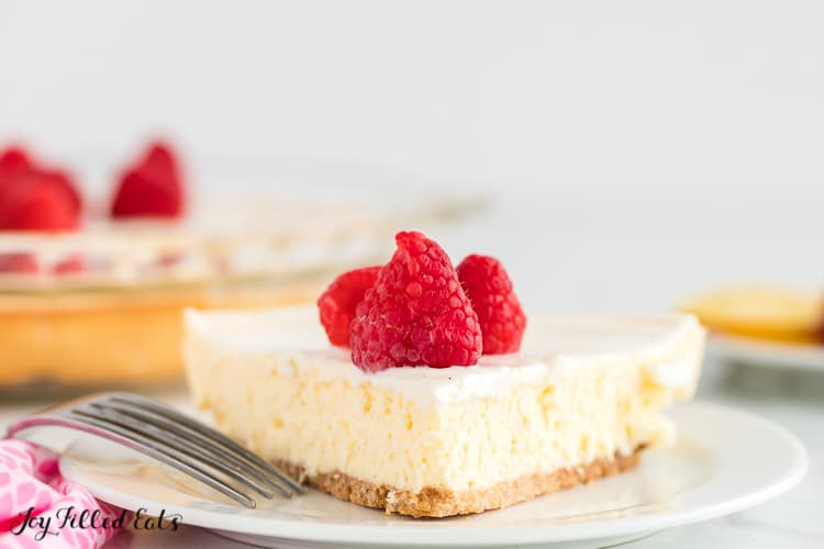 Lemon Cheesecake with Sour Cream Topping and raspberries on a white plate with a fork