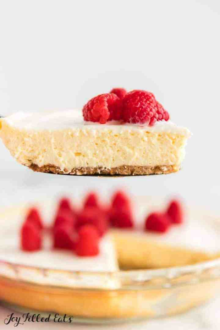 a slice of keto lemon cheesecake with sour cream topping lifted up with a pie server