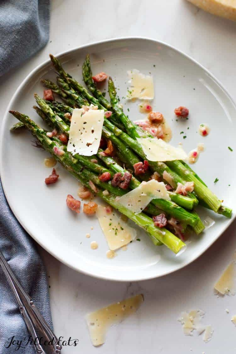 oven roasted asparagus with proscuitto on a plate with dijon vinaigrette and parmesan