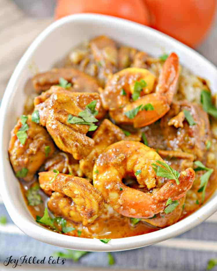 white bowl with shrimp curry and indian chicken curry