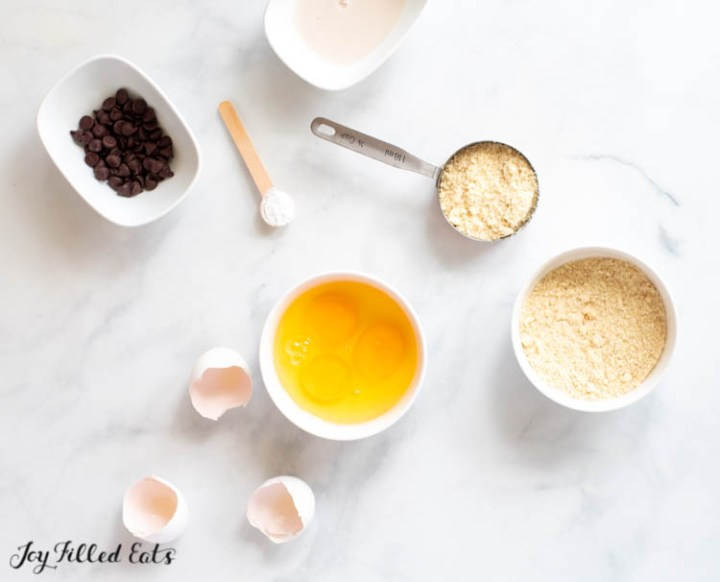 ingredients for the almond flour pancakes in small bowls: chocolate chips, eggs, almond flour, sweetener