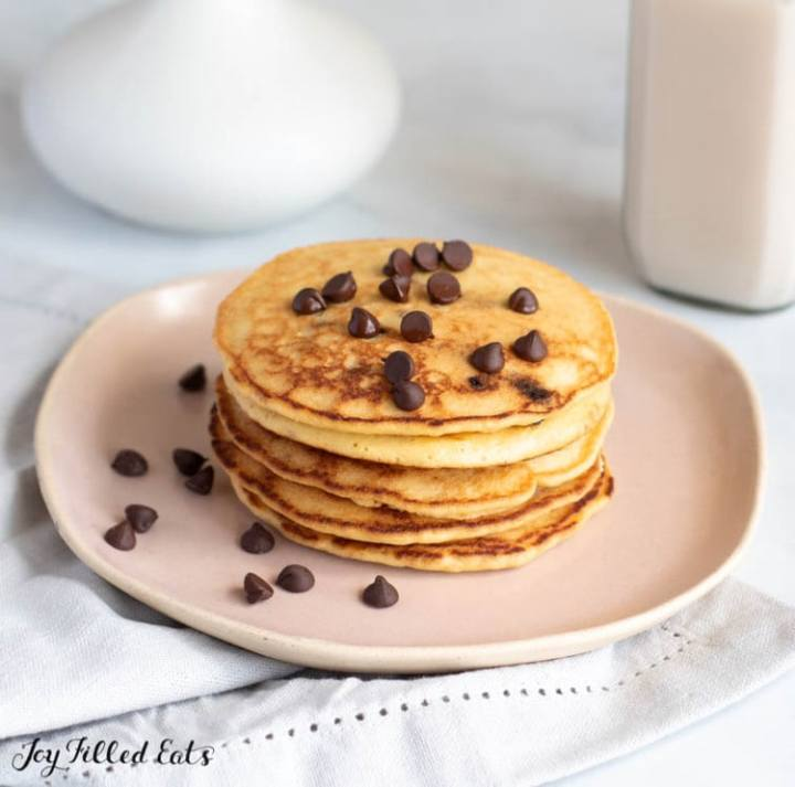 stack of keto pancakes on a plate with a sprinkle of chocolate chips on top