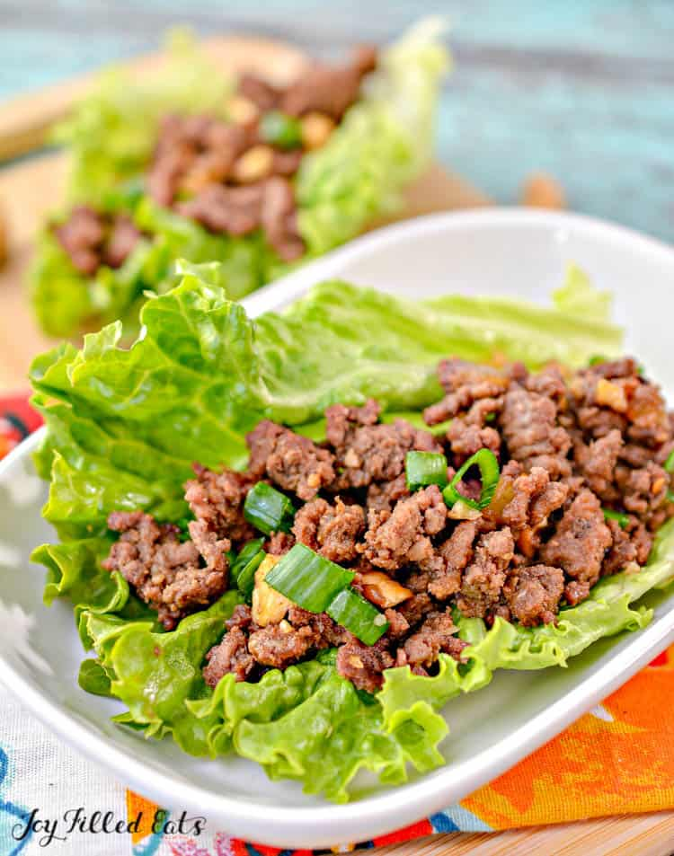 an asian lettuce wrap with beef on a white plate topped with chopped green onions