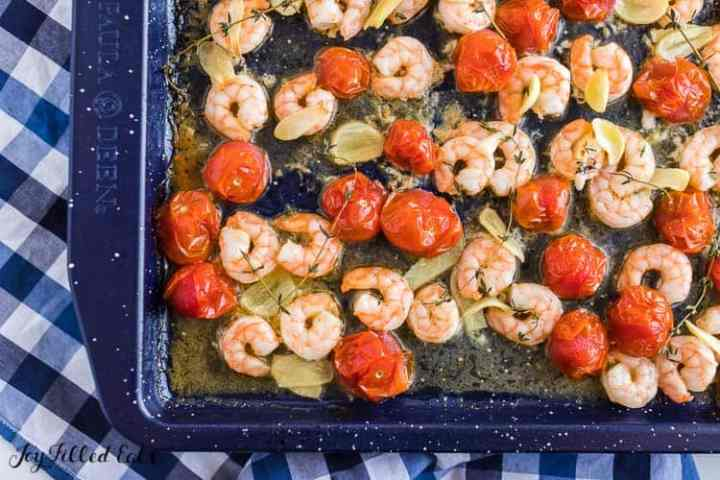 a baking sheet with cooked shrimp with garlic, tomatoes, and thyme