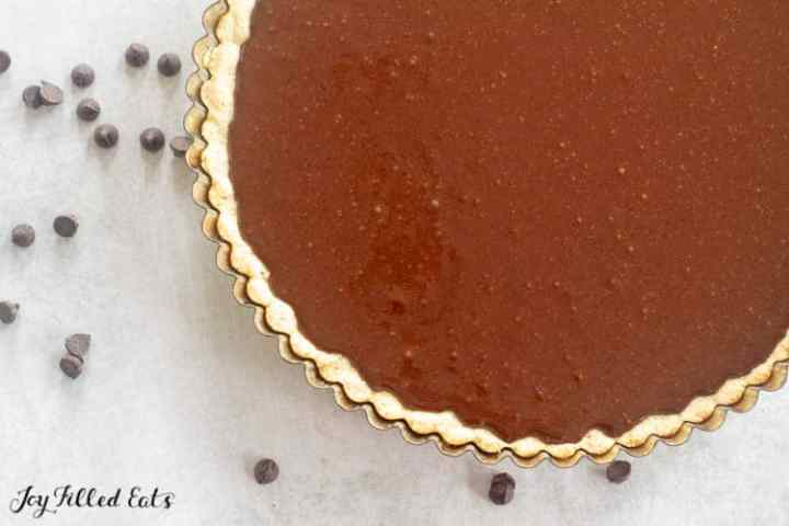 chocolate ganache poured into a baked tart crust