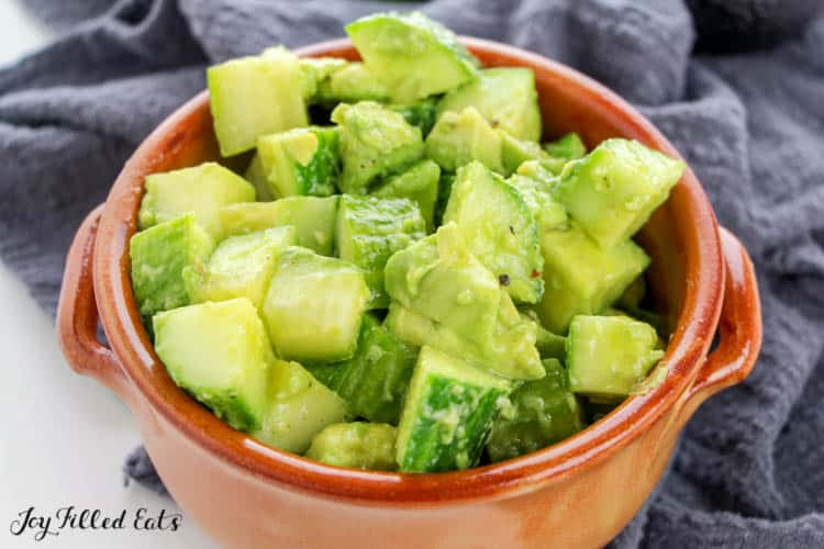 a bowl of cucumber avocado salad with a dark towel under it