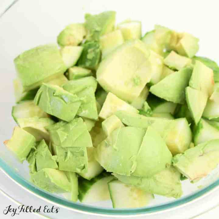 a glass bowl of chopped avocado and cucumbers