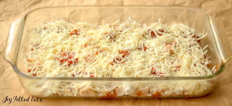 the cooked chicken in the dish topped with mozzarella