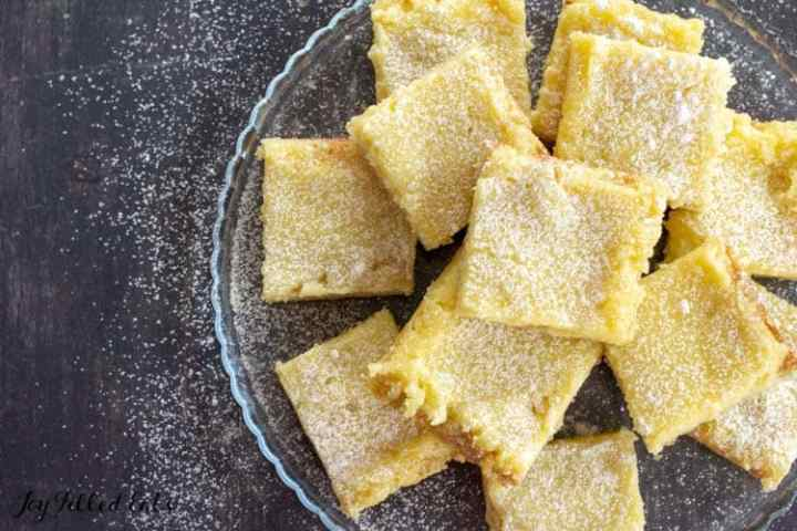 lemon squares on a glass plate sprinkled with powdered sweetener