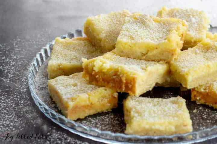 healthy lemon bars stacked up on a glass serving plate