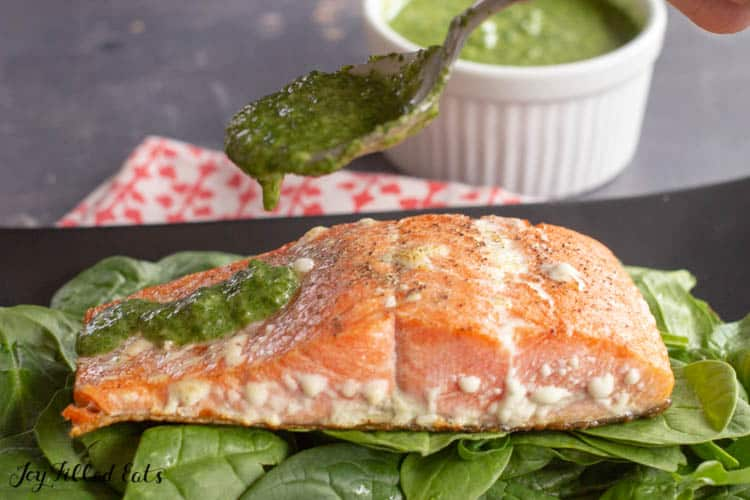 a spoon drizzling pesto on top of the salmon