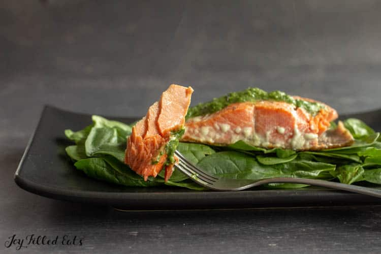 a fork with a piece of flakey pesto salmon and steam rising