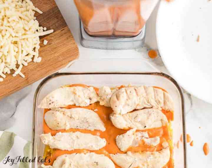 chicken tenders in the casserole dish on top of the pink sauce