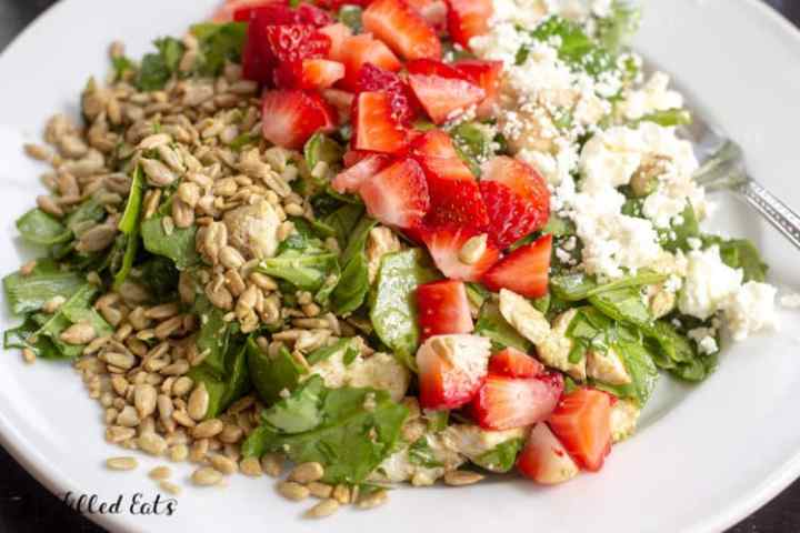 a white plate of baby spinach salad with strawberries, feta cheese, and sunflower seeds