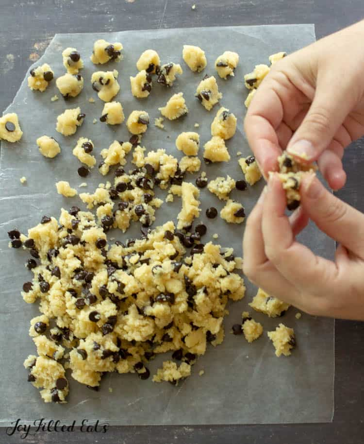 hands forming tiny balls of cookie dough