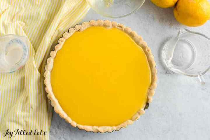 a lemon curd tart ready to be chilled