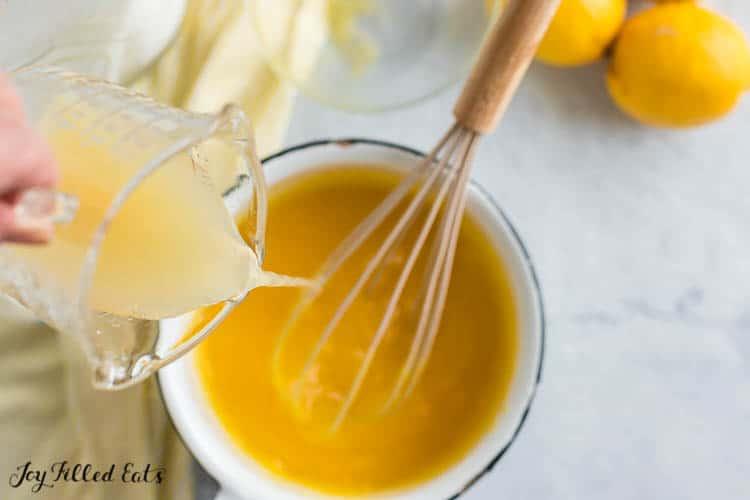 a hand pouring lemon juice into a small pot for lemon curd