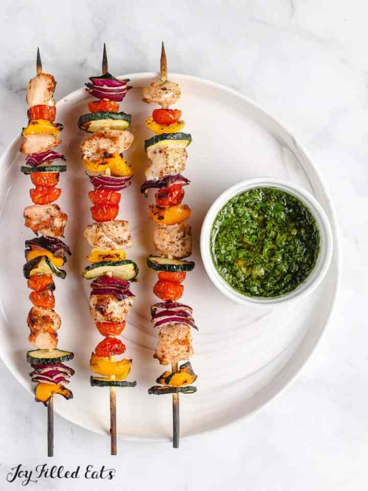wooden skewers with chicken and vegetables and chimicurri sauce
