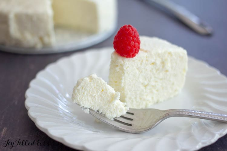 a fork with a bite of mascarpone cheesecake on a white plate