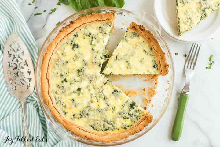 overhead shot of the spinach and feta quiche in a glass pie plate with a couple pieces missing