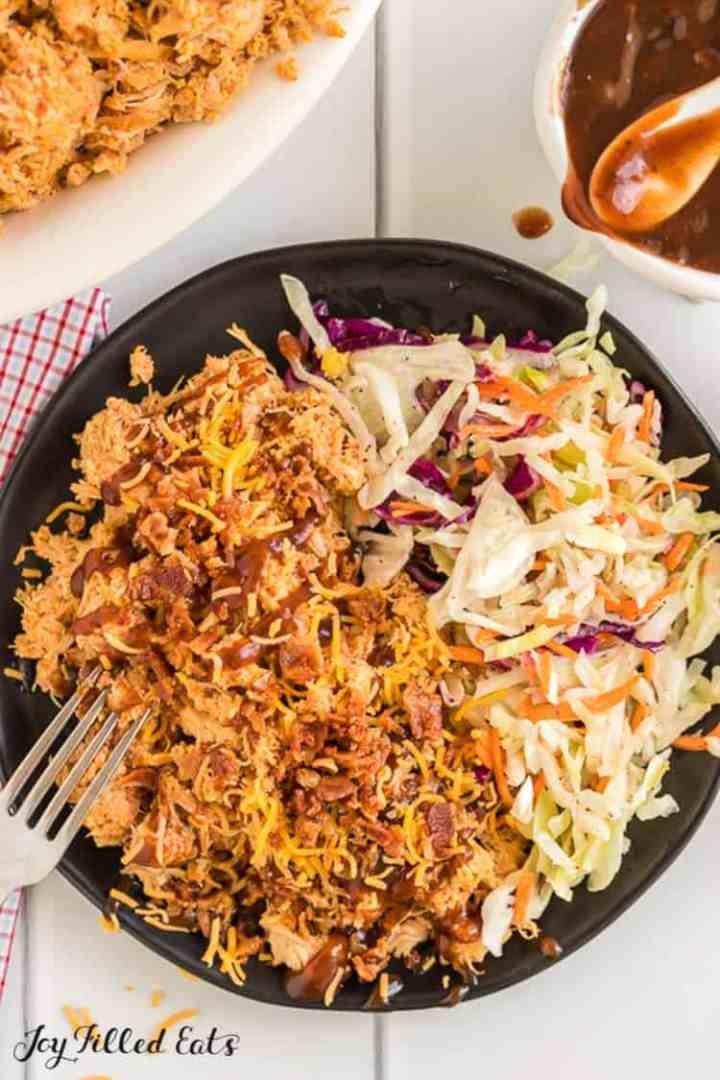 a black plate with crockpot bbq chicken and cole slaw