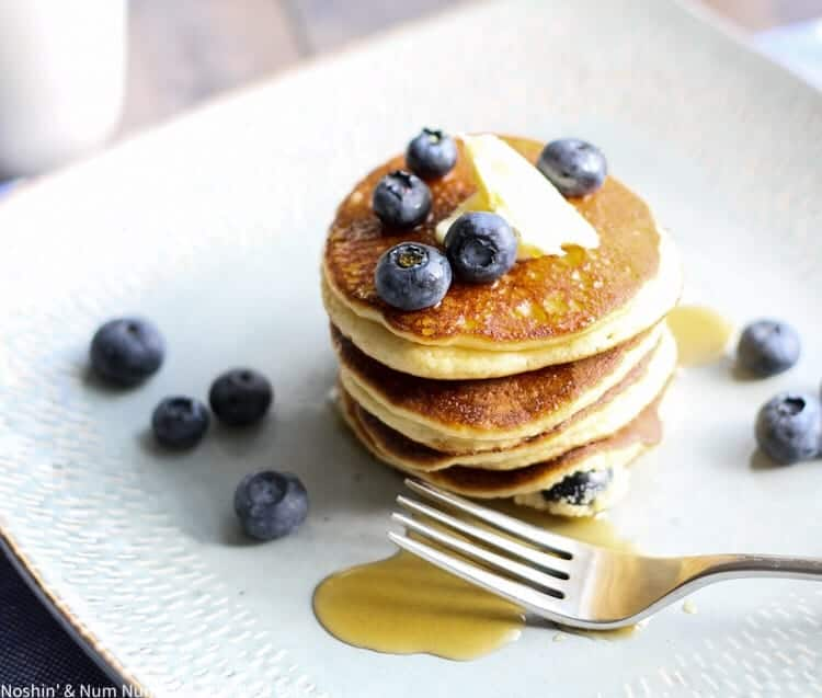 a stack of ricotta pancakes with blueberries on a white plate