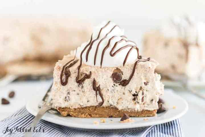slice of cannoli cheesecake on a plate topped with whipped cream and chocolate drizzle