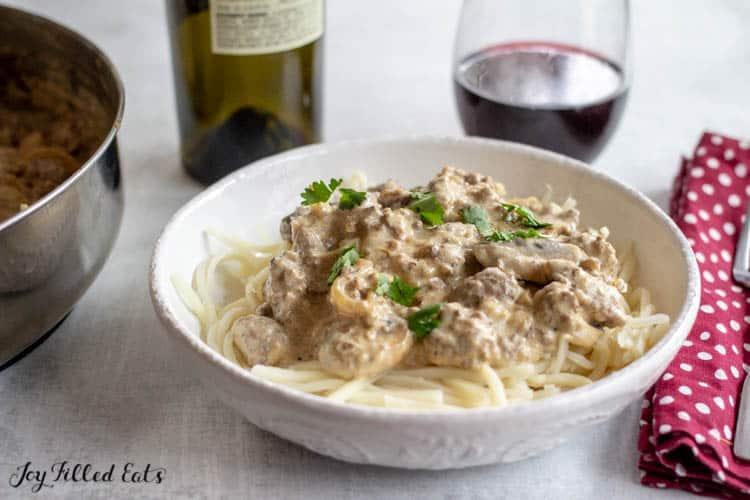 Ground Beef Stroganoff served in a bowl next to wine