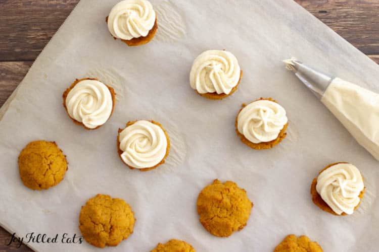 cream cheese icing being piped on cookies