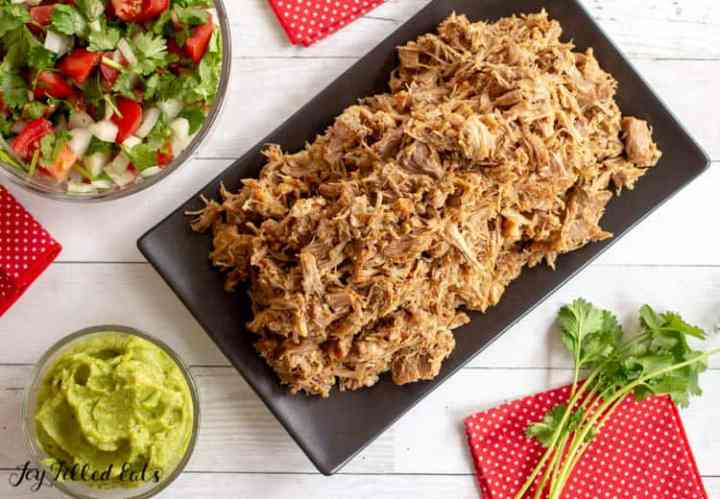 Instant Pot Carnitas on a serving platter with smaller bowls of pico de gallo and guacamole