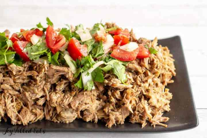 black serving platter topped with shredded pork carnitas and pico de gallo