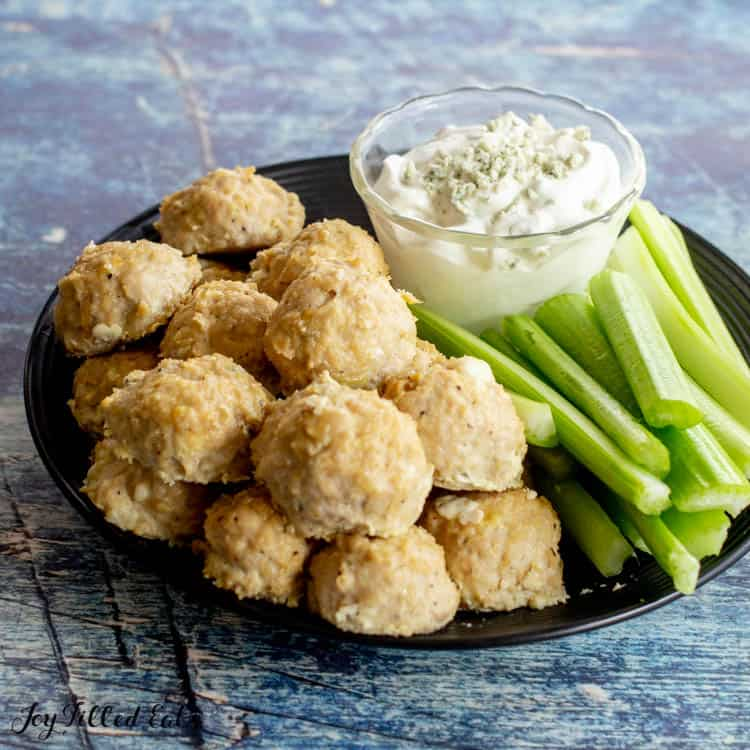 a serving platter with buffalo chicken meatballs, celery sticks, and blue cheese dip