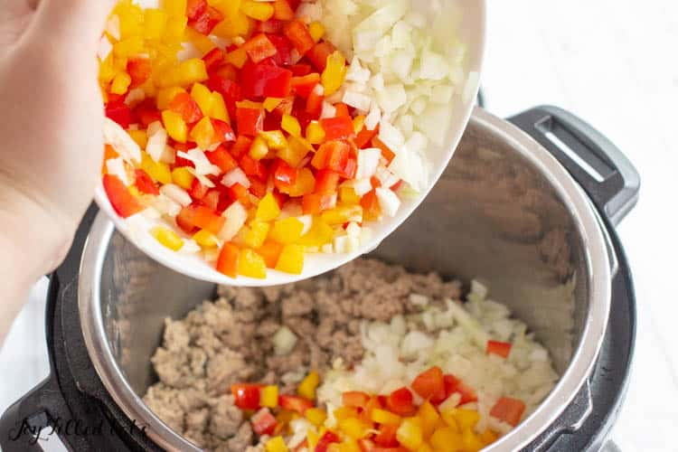 a hand pouring chopped onions and peppers into the instant pot