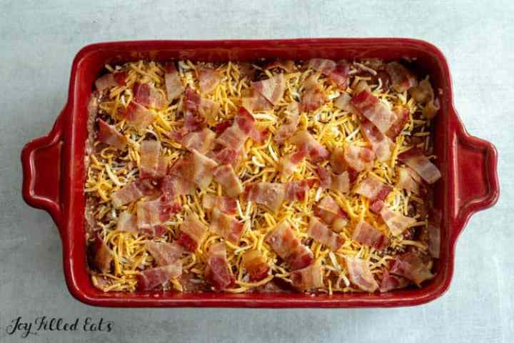 meat in a baking pan topped with cheese and bacon