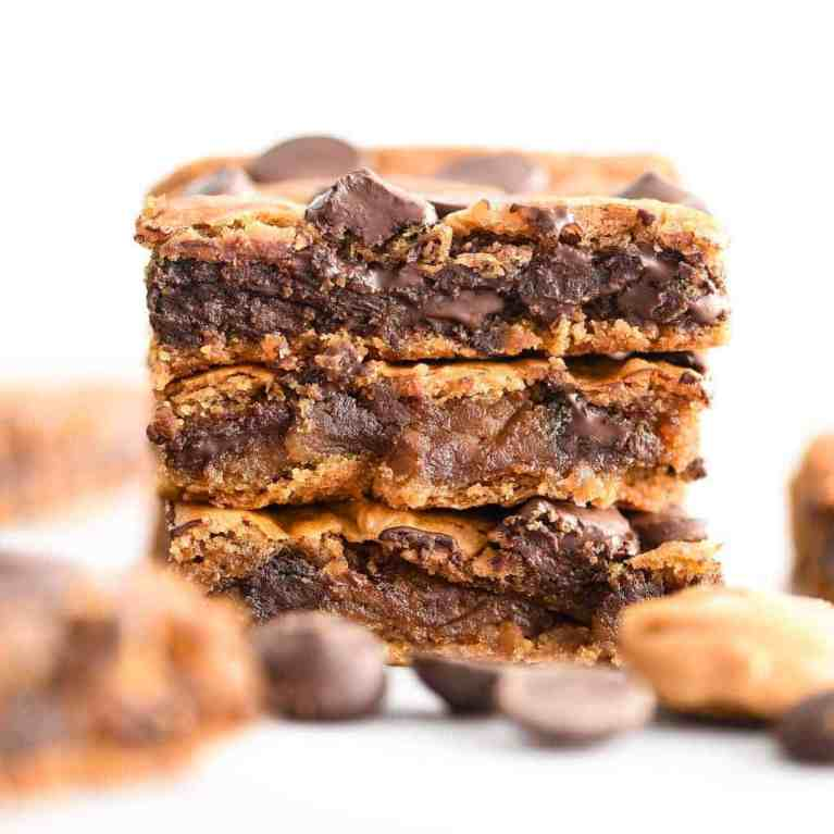 Up-close front view of a stack of three healthy peanut butter blondies with melty chocolate fresh from the oven