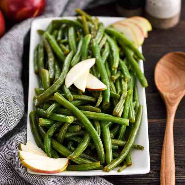 Front view of Sautéed Green Beans with Apple Cider on a serving dish garnished with apple slices