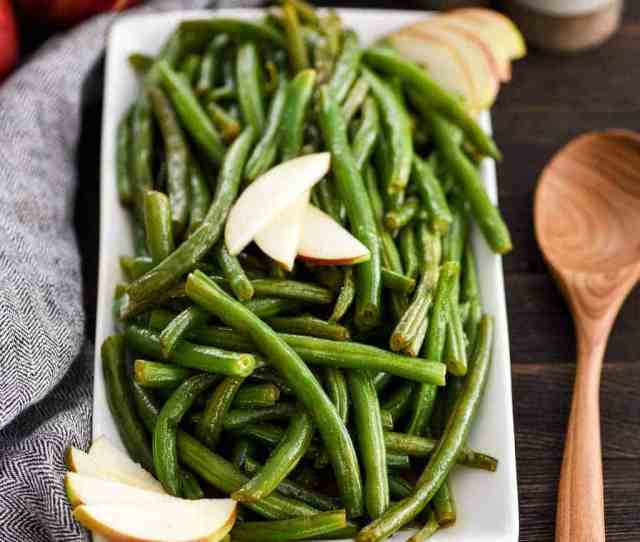 Front View Of Sauteed Green Beans With Apple Cider On A Serving Dish Garnished With Apple