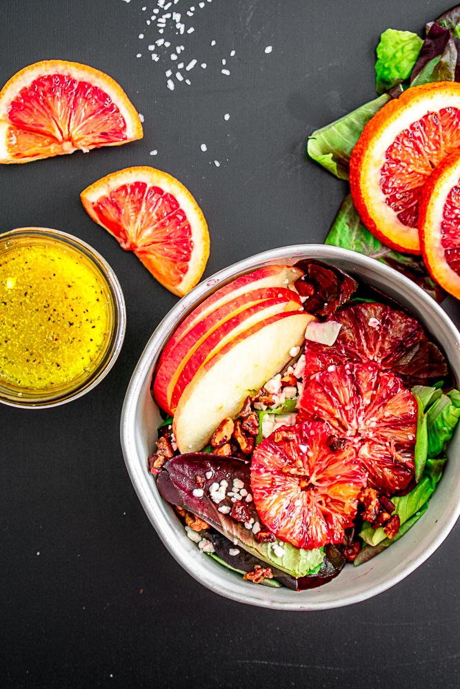 Blood orange salad in a bowl next to vinaigrette and orange slices